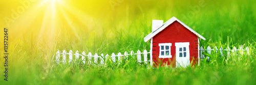Poster Jardin red wooden house model on the grass in garden