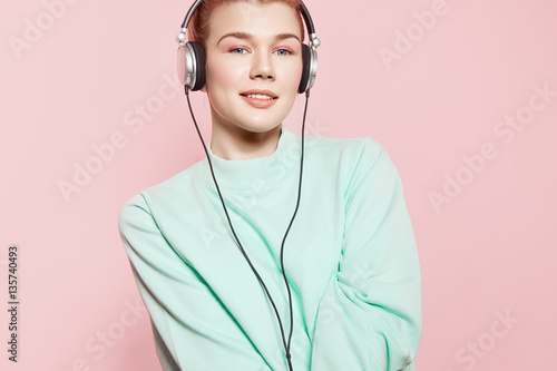 Poster womenART Smiling girl in headphones listening to music and standing on a pink background in a blue sweatshirt
