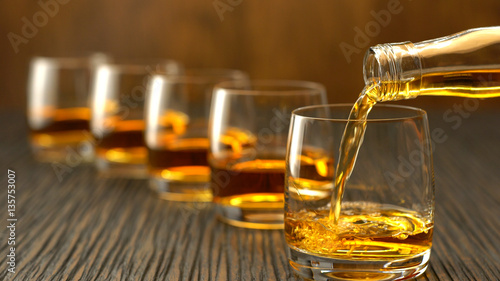 Pouring whiskey into the glass on a wooden table