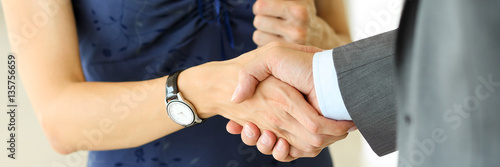 Fotografia  Businessman and woman shake hands as hello in office closeup