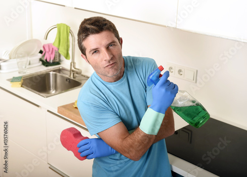 Fototapety, obrazy: young happy man holding washing detergent spray bottle and sponge in gloves smiling confident