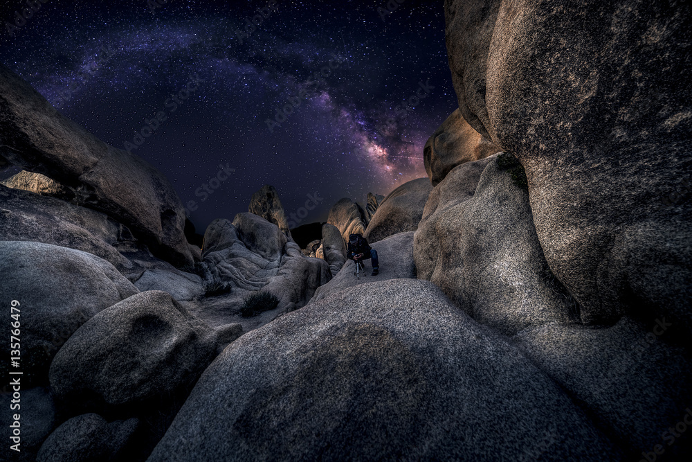 Fototapeta Photographer doing astro photography in a desert nightscape with milky way galaxy.  The background is stary celestial bodies in astronomy.  The heaven depicts science and the divine.