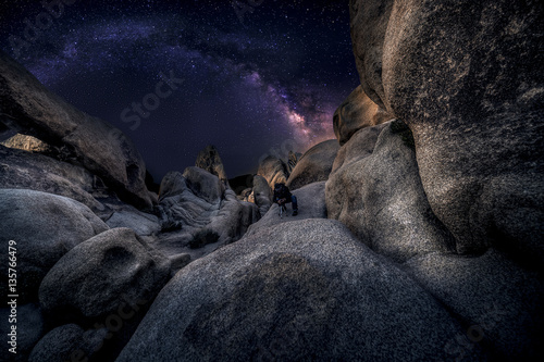 Fototapeta Photographer doing astro photography in a desert nightscape with milky way galaxy.  The background is stary celestial bodies in astronomy.  The heaven depicts science and the divine. obraz