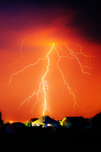 Cloud To Ground Electric Lightning Behind House Roof Tops
