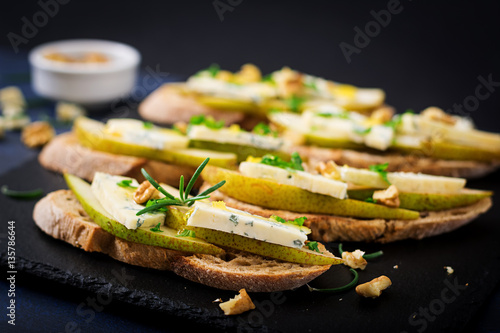 Cadres-photo bureau Entree Bruschetta sandwich with pear, blue cheese, honey and nut on a dark background.