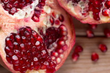 Pomegranate slices and garnet fruit seeds on table