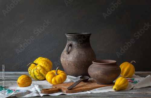 Still life in a rustic style: autumn harvest: wicker basket, pumpkins and wooden spoon on a  table. Natural light from a window.
