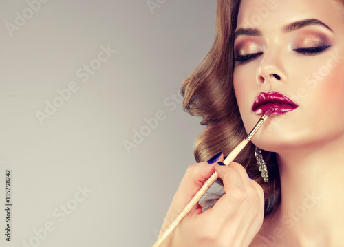 Fotografía  Hand of make-up master, painting lips of young beautiful model
