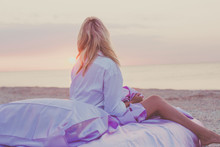 Blond Woman Wakes Up On The Beach, Sitting In A Bed Of Silk On The Sand, Wearing A Man's Shirt, Meditating, Greets The Dawn