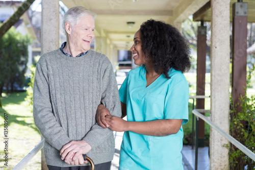 Fotografie, Obraz  African nurse assisting elderly man outdoor