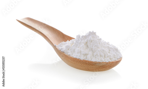 Pile of white wheat flour in wooden spoon