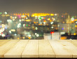 Bokeh blurred of Pattaya city at night montage with wood table top for background.