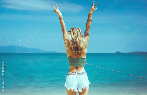 Fotografie, Obraz  pretty woman posing in the sea, blue sky, hair wild, victory hand up!, outdoor p