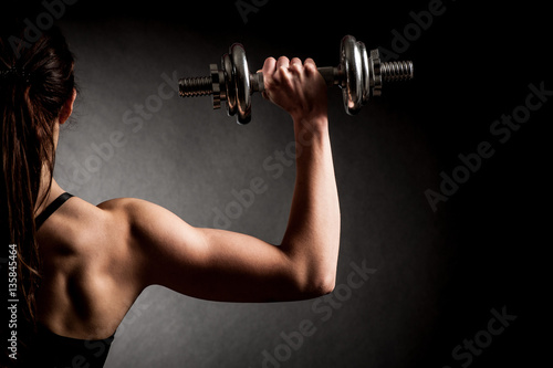 Tela Atractive fit woman works out with dumbbells as a fitness concep