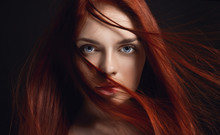 Sexy Beautiful Redhead Girl With Long Hair. Perfect Woman Portrait On Black Background. Gorgeous Hair And Deep Eyes. Natural Beauty, Clean Skin, Facial Care And Hair. Strong And Thick Hair. Flower