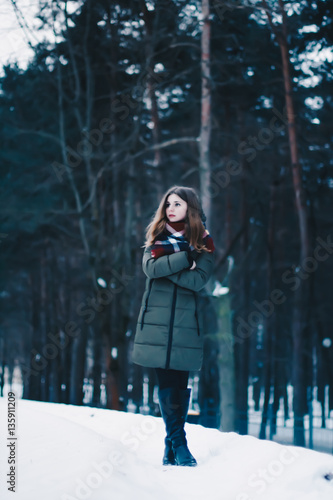 Beautiful young girl frozen, lost, warming his hands from