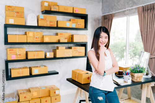 Young Asian small business owner at home office, online marketing packaging and delivery scene, startup SME entrepreneur or freelance woman working at home concept