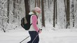 Slow shot at a woman who goes through the snowy forest. Around her grow tall and massive trees. Woman warmly dressed in a white tank top, black pants, a pink hat and gloves.