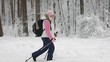 The woman in the winter wood. The pensioner works the Scandinavian walking. The Scandinavian walking is very useful to health. The woman for a healthy lifestyle.