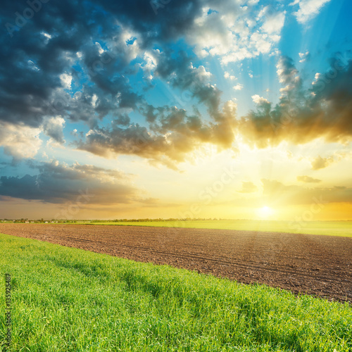 Poster Heuvel sunset in cloudy sky over agricultural fields