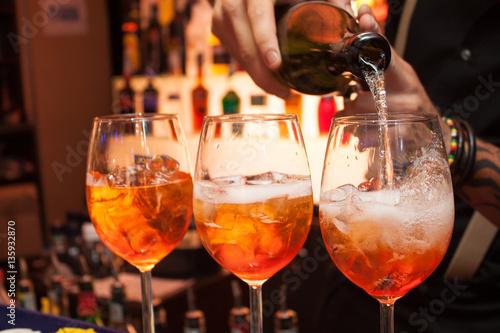 tre cocktail Aperol al bar. Il barista versa champagne in un bicchiere