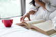 Woman relax and reading on the bed with old book