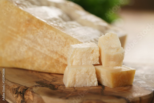 Staande foto Zuivelproducten hard parmesan cheese cubes on olive cutting board, closeup photo
