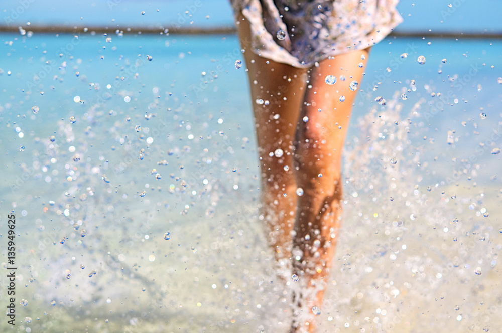 Fototapety, obrazy: Young slim fit woman making water splashes with her legs. Vacation and summer mood