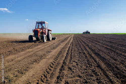 Foto  Tractors sowing on agricultural fields on beautiful sunny spring day