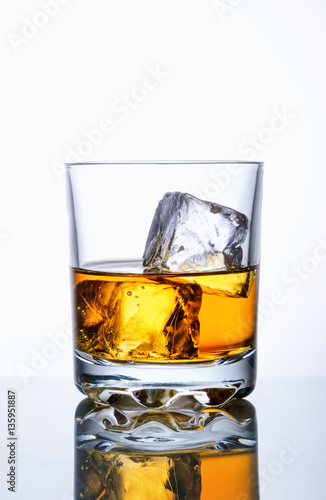 Spoed Foto op Canvas Bar Whiskey glass with two ice cubes on white glass surface over white background