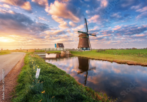 Windmill near the water canal at sunrise in Netherlands Canvas Print