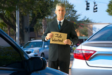 Unemployed Panhandler Man At Traffic Intersection With Job Wanted Sign Painted On A Piece Of Cardboard Begging For Work As He Tries To Survive In Ever Changing Difficult Times