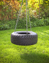 An Old Rubber Tire Swing On Chains In A Backyard For Kids To Pla