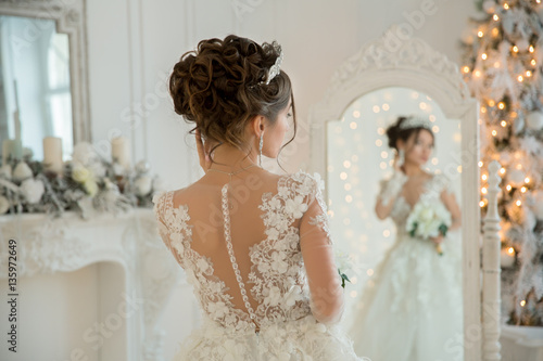 Stampa su Tela Beautiful bride in a wedding dress at a mirror in Christmas. Gir