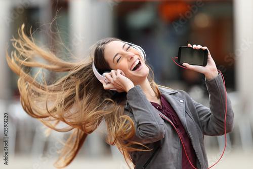 Plakat Dziewczyna taniec i słuchanie muzyki na ulicy