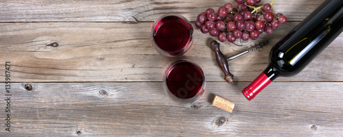 Poster Wine Unopen bottle of red wine and glasses with grapes on rustic wood