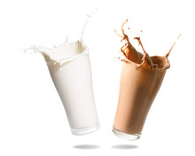 Milk And Chocolate Milk Splashing Out Of Glass., Isolated White Background.