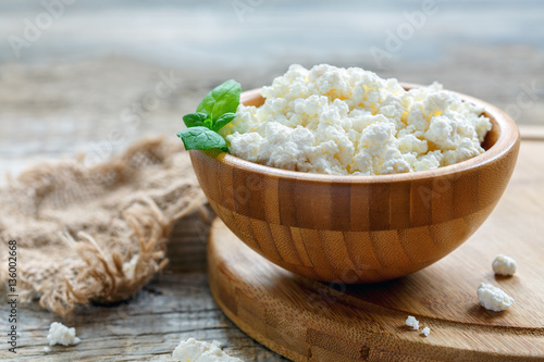 Poster Dairy products Fresh cottage cheese and mint in a wooden bowl.