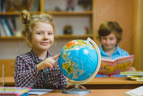 Plakát  smiling girl showing on globe at school classroom