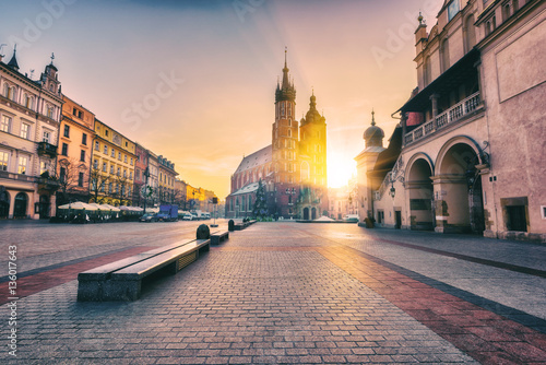 Fotobehang Krakau Krakow, main architectural ensemble, amazing colors of sunrise over the old town Market square, St. Mary's church (Mariacki cathedral) and Cloth Hall (Sukiennice), Poland, Europe