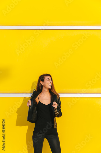 Cool trendy girl posing over a yellow wall