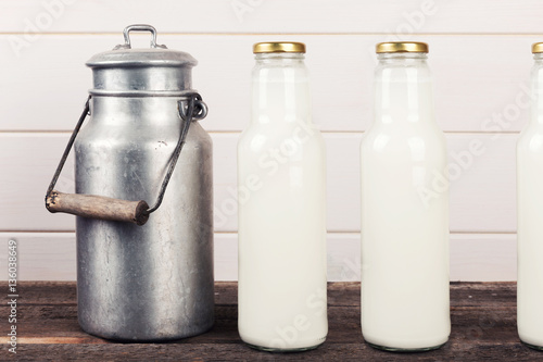 old milk can and bottles on wooden table
