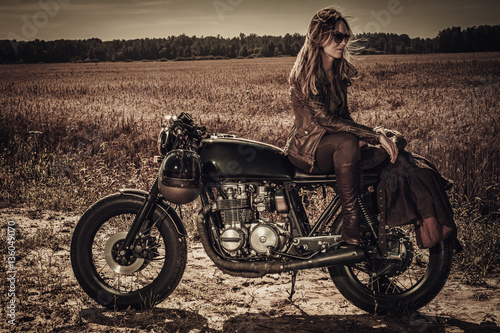 Young, stylish woman on vintage custom cafe racer in field Fototapeta