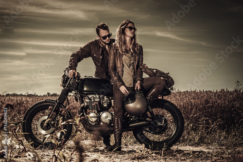 Stampa su Tela Young, stylish cafe racer couple on vintage custom motorcycles in field