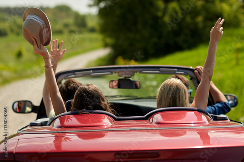 happy friends driving in cabriolet car at country - 136054866