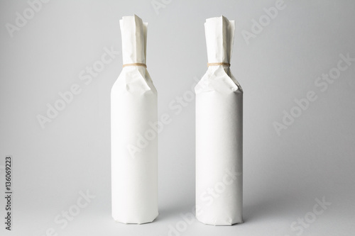 Fotografía Two wine bottles are standing on gray background