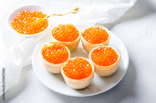 Red caviar tartlets, appetizer canapes on bright background