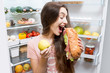 Young woman choosing between apple and big sandwich standing in front of the refrigerator full of vegetables and fruits