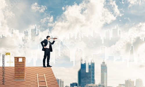 Poster Abou Dabi Engineer man standing on roof and looking in spyglass. Mixed med