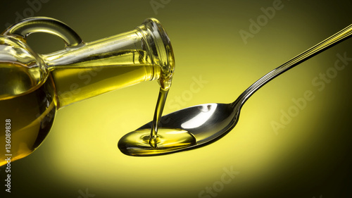 bottle pouring oil in a spoon on green background